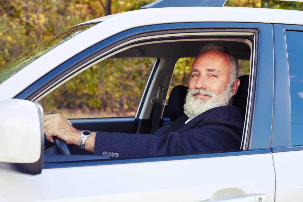 Older man with a gray beard behind the wheel in a vehicle.