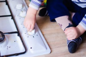 The hand of an unattended child is shown playing with the knobs of a stove.