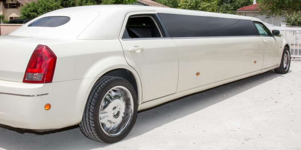 long white limousine pulling up to a gate