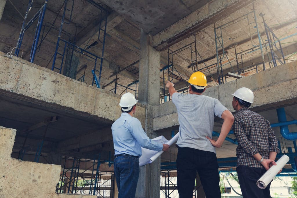 Three men in construction hard hats stand at a construction job site. One in the middle in a yellow safety helmet point up at the second level on the site.