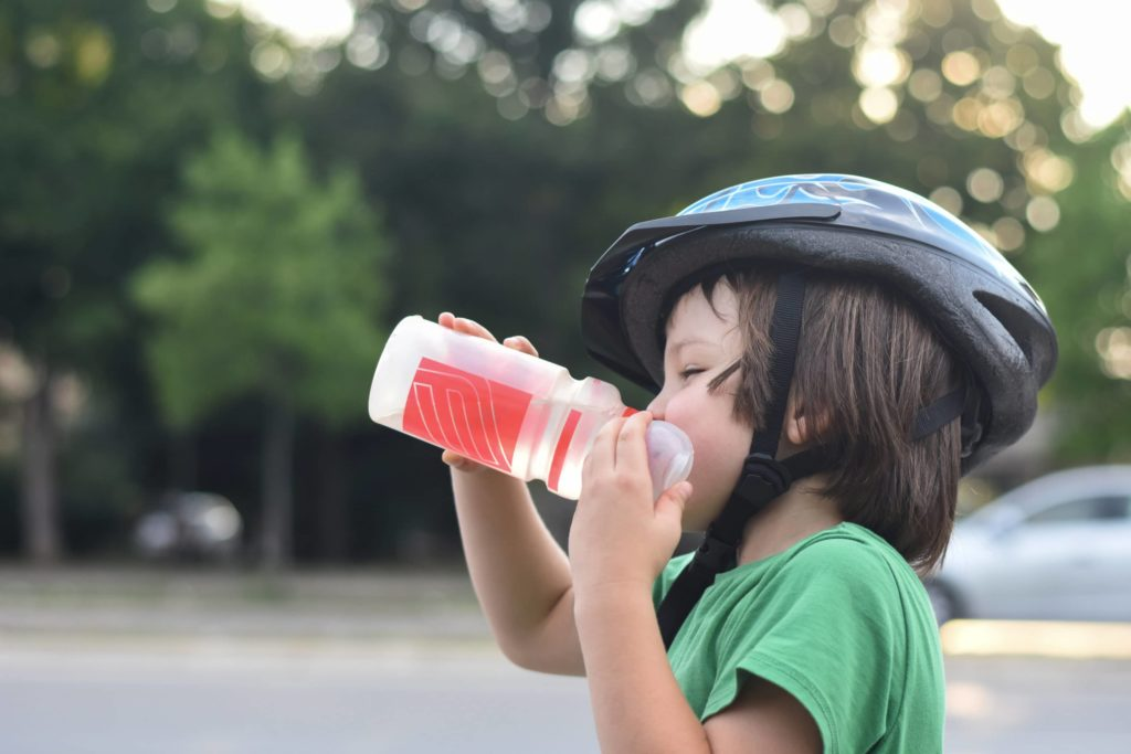 Child wearing a bike helmet and green shirt drinks from a water bottle