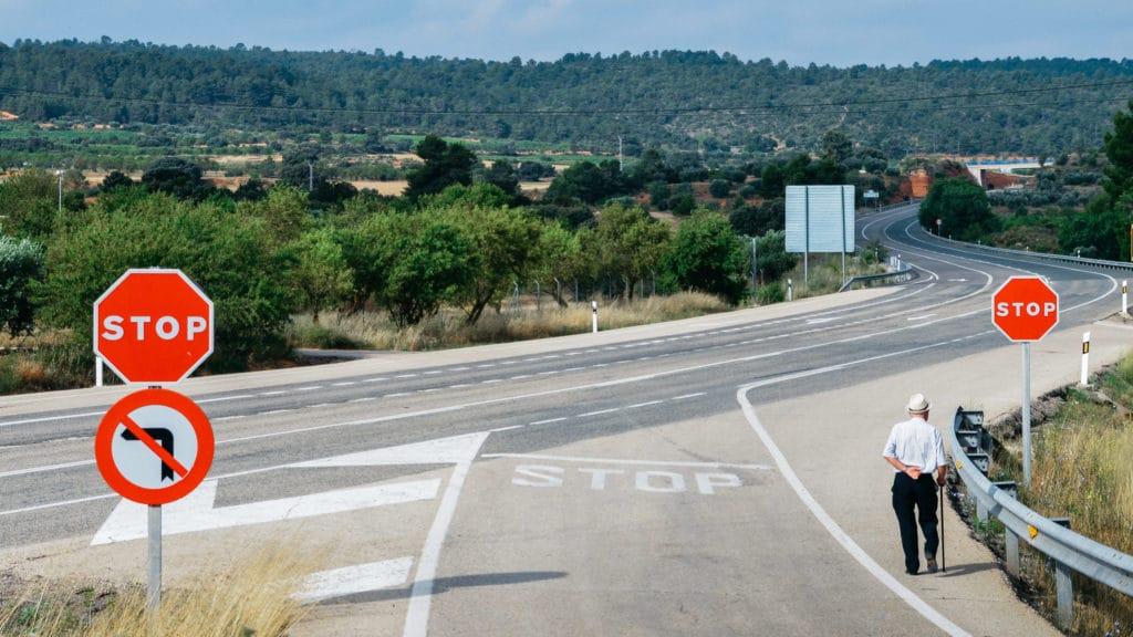 Older gentleman walks along the highway on an open road