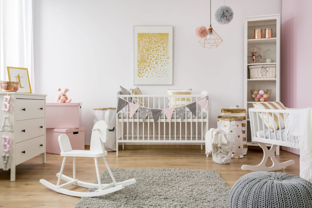 child's room with rocking chair, crib, changing table, and pink and white color scheme.