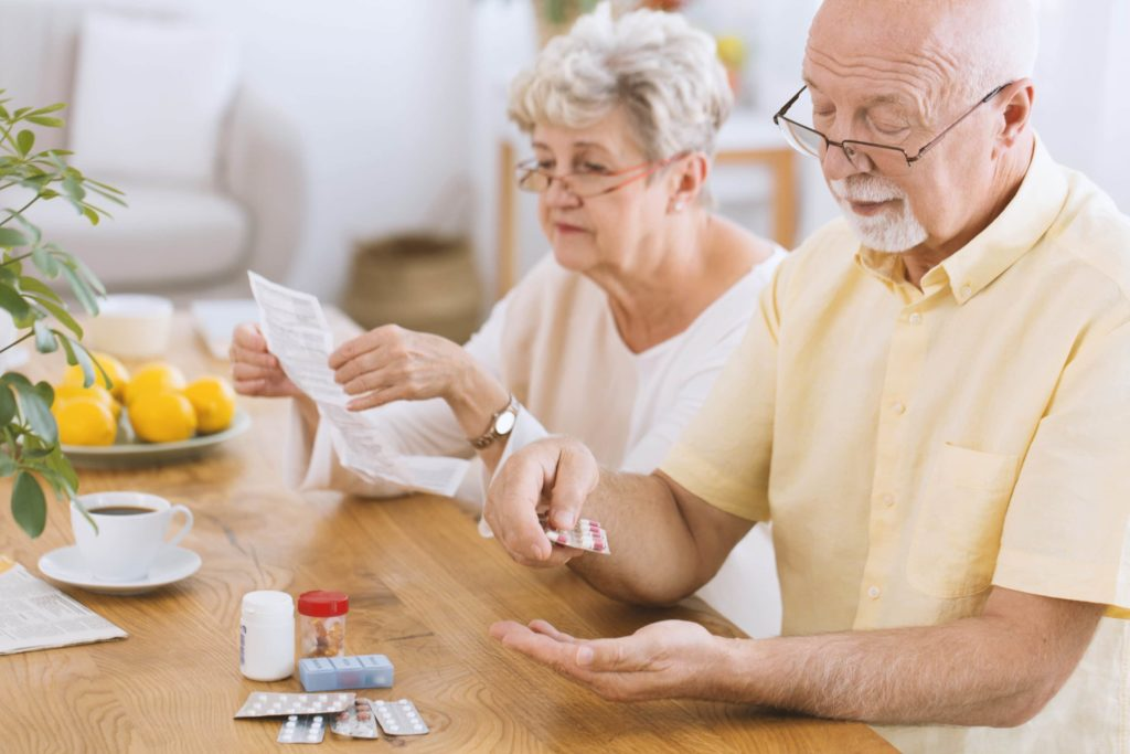 An elderly couple sits at a table. One takes medication while the other reads documentation.