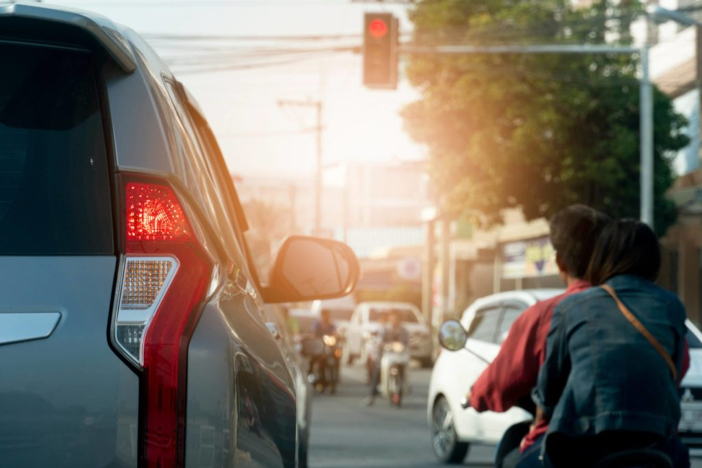 A car and motorbike wait at a red light at a busy intersection with the sun setting in the background.