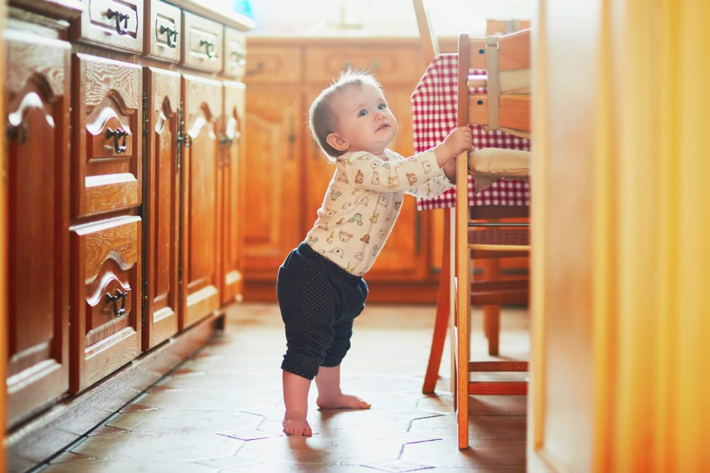 A baby stands herself up by holding onto a chair in a light-filled kitchen