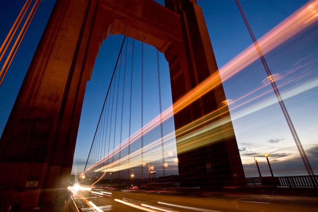 cars drive under a bridge at dusk