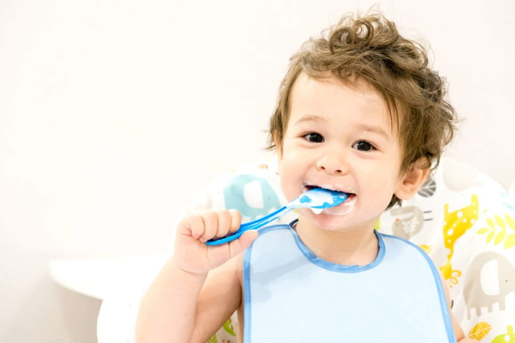 smiling child with a blue bib on puts a spoon in their mouth