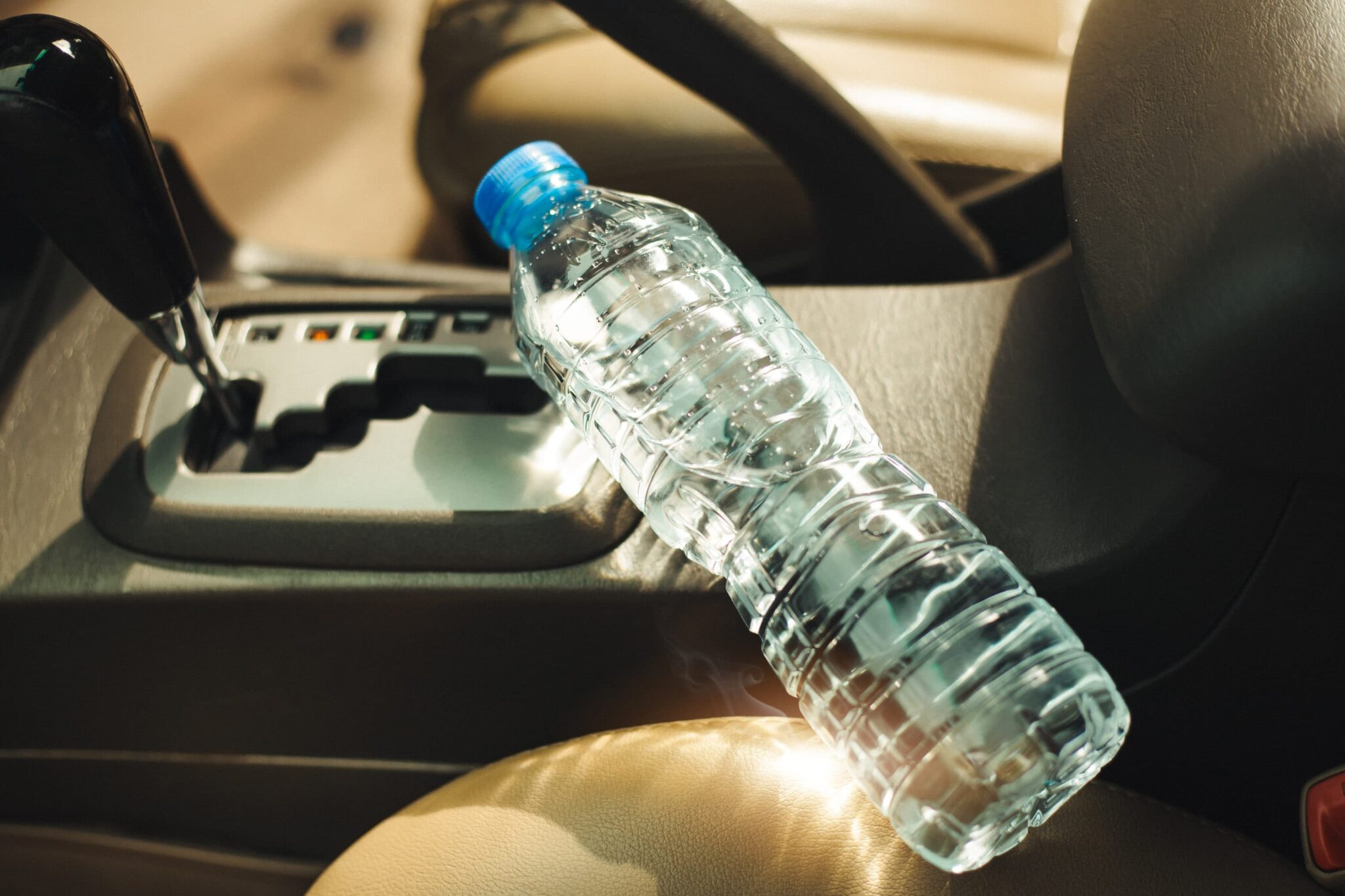 plastic water bottle sits on the gear stick in the car in the sunlight