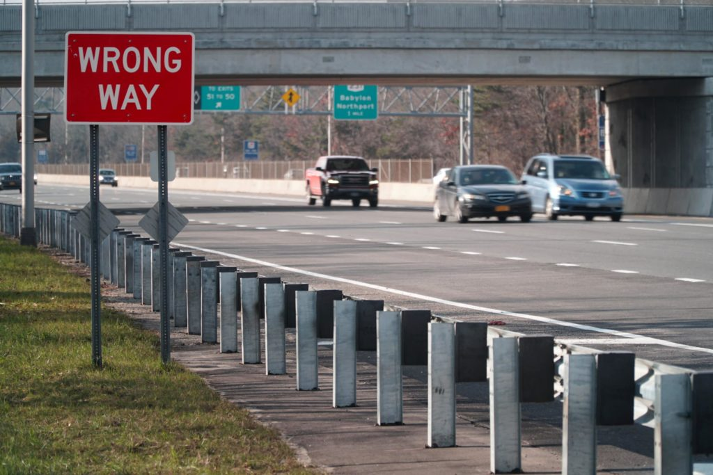 cars drive on a highway with a wrong-way sign in the foreground