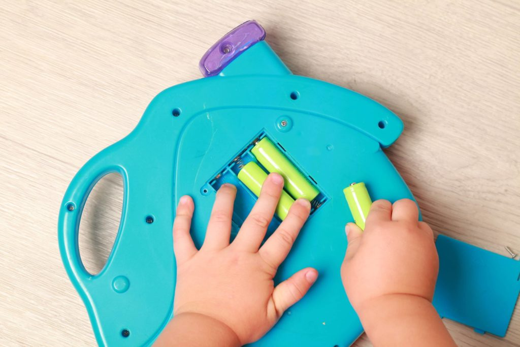 baby hands take batteries out of the back of a blue toy