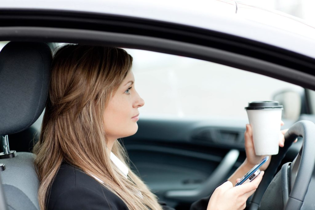 Woman in black suit jacket sits distracted behind the wheel in the driver seat with her phone and a coffee in her hands.